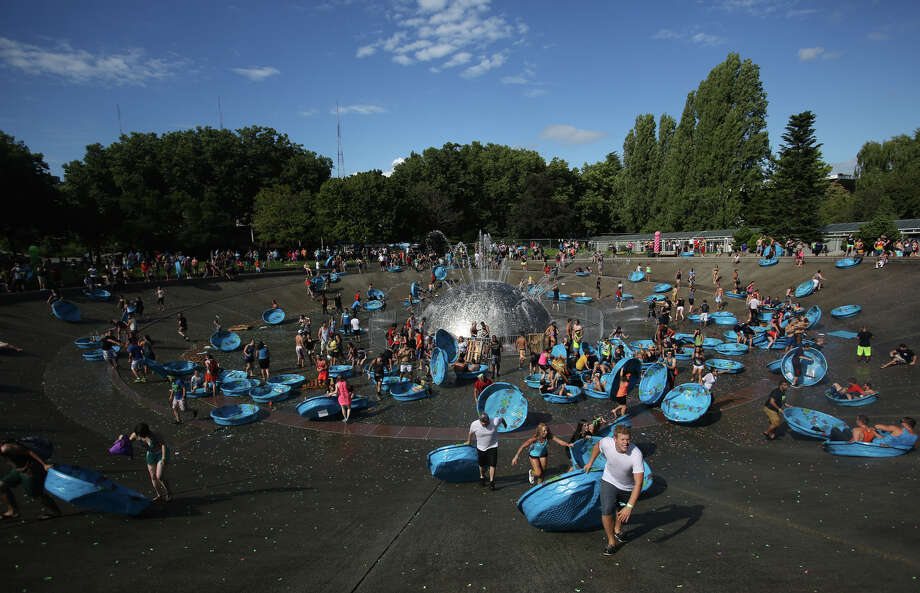 Kiddie pools used to hold water balloons are used to slide down the sloped walls of the International Fountain. Photo: JOSHUA TRUJILLO, SEATTLEPI.COM / SEATTLEPI.COM