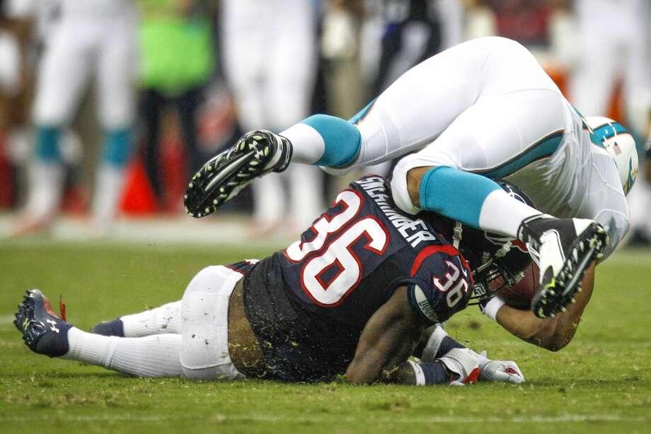 Texans safety D.J. Swearinger upends Miami tight end Dustin Keller, causing a knee injury for Keller. Photo: Brett Coomer, Houston Chronicle