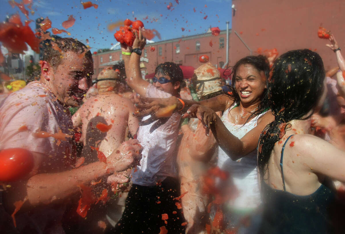 Hundreds of attendees throw tomatoes at each other during the 3rd annual Seattle Tomato Battle on Saturday, Aug. 17, 2013, at the Pyramid Brewery in Seattle.