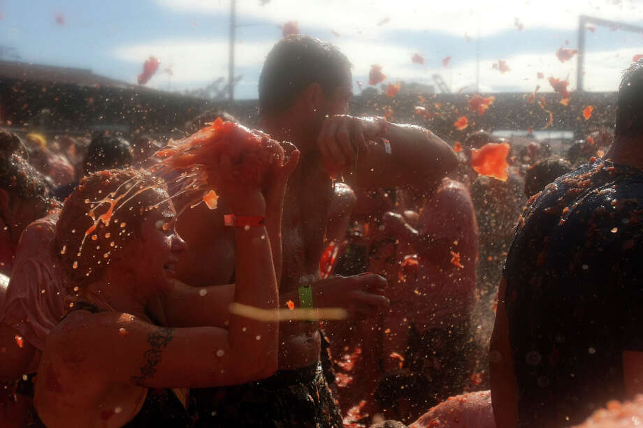 Hundreds of attendees throw tomatoes at each other during the 3rd annual Seattle Tomato Battle on Saturday, Aug. 17, 2013, at the Pyramid Brewery in Seattle. Photo: SY BEAN, SEATTLEPI.COM / SEATTLEPI.COM