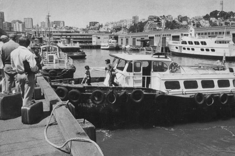 "Seamen wait at Pier 9 to board Crowley Maritime water taxi ""Mallard."" June 16, 1978. Photo: Jerry Telfer, The Chronicle"