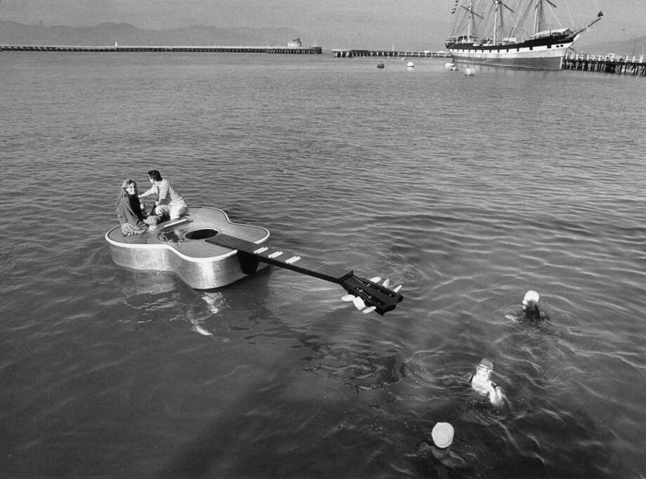 Three members of the Dolphin Club just couldn't believe their eyes one morning after finishing up a dip in the Bay. It was the maiden voyage of an 18-foot outboard motorboat built in the shape of a guitar by Don Price of Santa Rosa. After its voyage, it was on display at the Sports and Boat Show at the Cow Palace. January 2, 1989. Photo: Brant Ward, The Chronicle