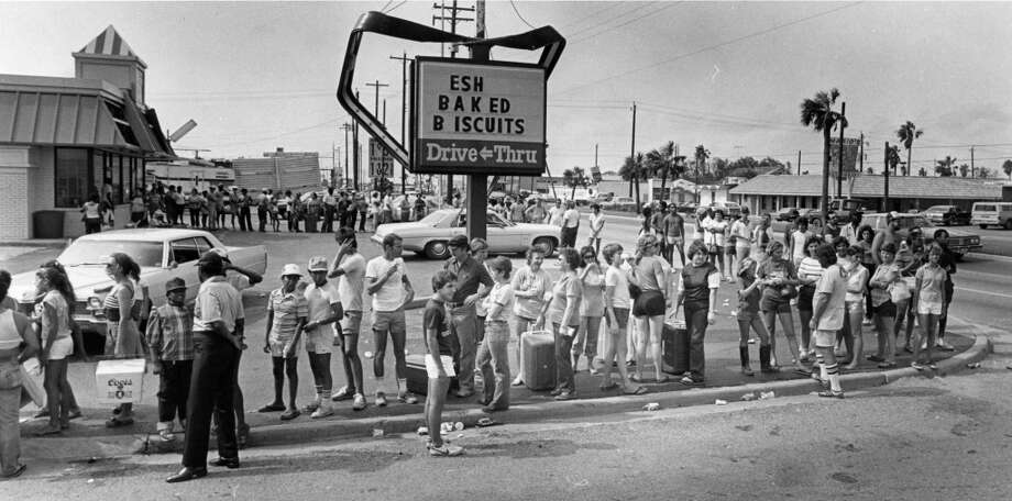 From the August 21, 1983, Houston Chronicle: Galveston residents waited more than two hours outside an ice company mini-warehouse on 61st Street to buy ice to prevent food from spoiling. The city's electric power, along with most phone service, was knocked out by Hurricane Alicia. The ice lines curled around a disfigured electric sign and a take-out restaurant with its roof damaged by the storm's winds of over 100 mph. Photo: John Everett, Houston Chronicle