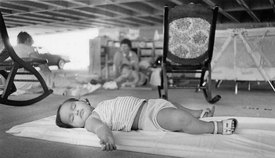Fourteen-month-old Rosanna Diaz, daughter of Patricia Diaz, slept in a temporary emergency child care center in the parking garage at Moody Center in Galveston Tuesday morning while adults stood in line to apply for federal aid, August 23, 1983 Photo: Joel Draut, Houston Post
