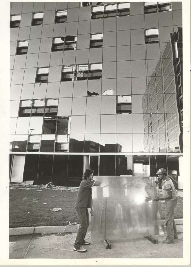 Downtown Houston was not the only area of the city in which the gleaming glass walls of skyscrapers were shattered by Alicia.  These workers, Ron Nelson, left, and Reginald Kingsberry, were at work replacing broken panes in an office building at 2929 Briarpark in the Westchase area.  Builders said they believed the damage to the panes was caused by wind-borne debris. Photo: Sam C. Pierson Jr., Houston Chronicle