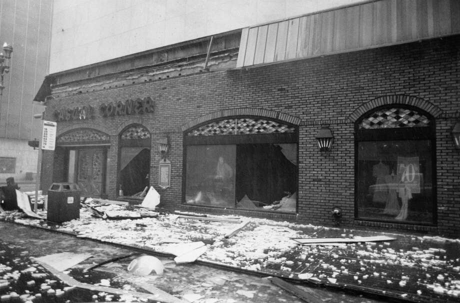 Shattered panes of glass and debris from this downtown store at 901 Main litter the sidewalk, making walking somewhat hazardous. Photo: King Chou Wong, Houston Post