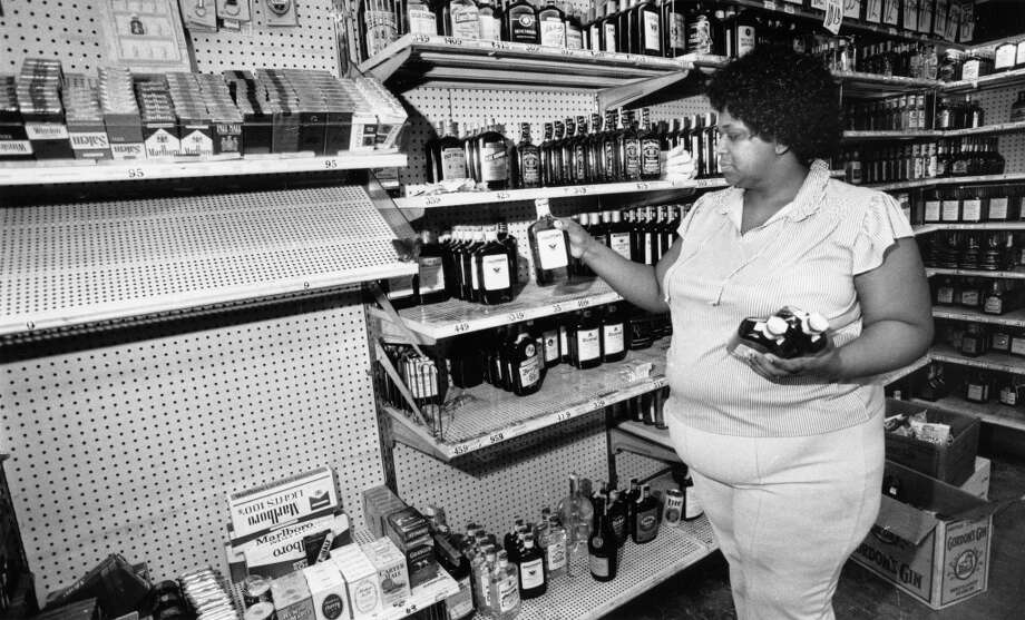 Alma Hall restocks liquor to shelves after looters struck at Ralston's, August 19, 1983. Photo: Audrey Ueckert, Houston Post