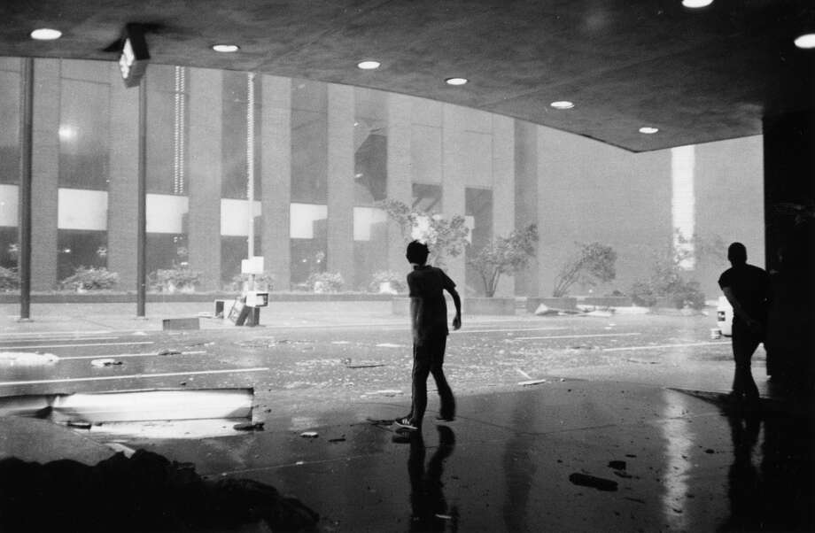 Spectators from the Sheraton Hotel view damage done to the Hyatt Hotel by Hurricane Alicia, August 18, 1983. Photo: King Chou Wong, Houston Post