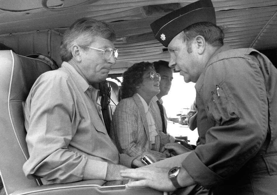 Leaving Hobby Airport, Texas Gov. Mark White gets instruction on safety from a National Guard official. At center is Houston Mayor Kathy Whitmire, August 19, 1983. Photo: Cathy Ambrose Smith, Houston Post