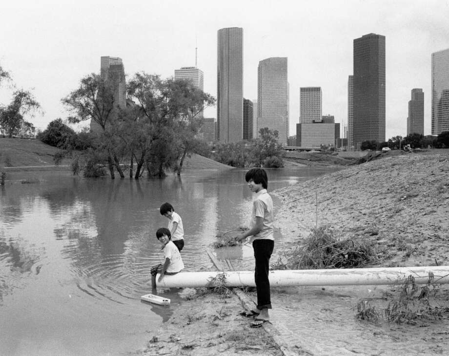 Kids play with a boat in flooded Buffalo Bayou between Memorial and Allen Parkway, August 19, 1983. Photo: Craig Hartley, Houston Post