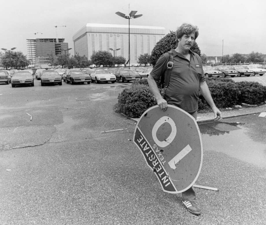Bob Morrison, an employee of Jarnagin Pontiac at 12111 Katy Freeway, picks up a sign that was blown into their car lot, August 18, 1983. Photo: Steve Campbell, Houston Chronicle