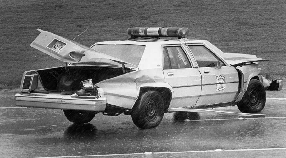 Houston Police car driven by officer T.A. Britt tried to avoid debris in the 2300 block of I-45. As he swerved, the wind picked up the rear end of the car and he drove into the median. August 18, 1983. Photo: Timothy Bullard, Houston Chronicle