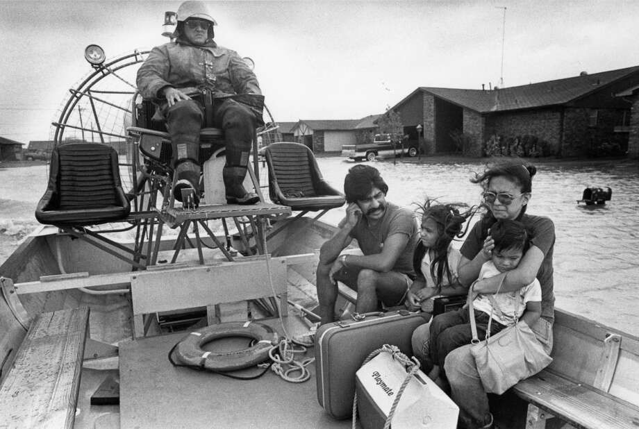 Houston firefighter Alex Arizpe evacuates Tony Lopez, Elma Lopez and their family, Anthony Lopez, 2 1/2, and daughter Faith Lopez, 7, from the Scarsdale area. August 18, 1983. Photo: Timothy Bullard, Houston Chronicle