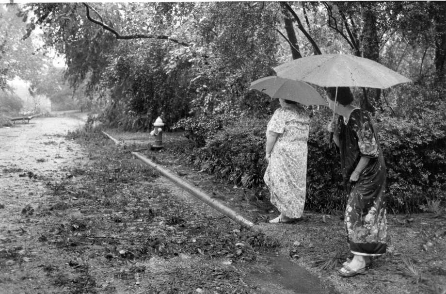 Madeline Koster, right, and her daughter, Becky Koening, very tentatively check the debris around their Glenwood subdivision home in the Memorial area. Photo taken August 18, 1983. Photo: Carrie Beth Tucker, Houston Chronicle