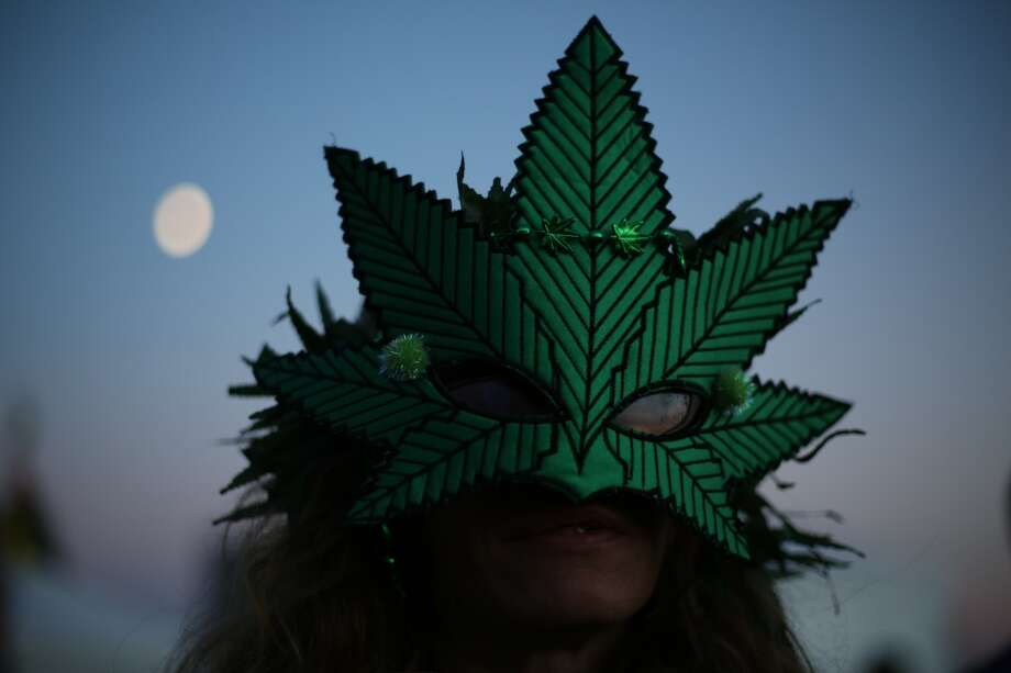 A participant wears a mask as the moon rises during the second day of Seattle's annual Hempfest. This is the first year for the annual pro-pot rally since Washington State voters legalized recreational use of marijuana. Photographed on Saturday, August 17, 2013. Photo: JOSHUA TRUJILLO, SEATTLEPI.COM