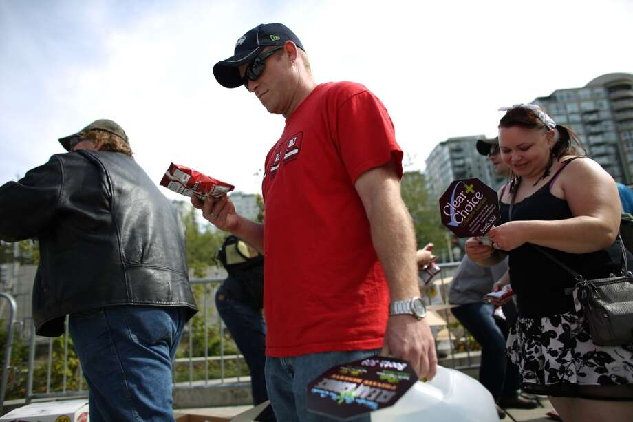 People read the message as Seattle Police officers hand out bags of Doritos with a sticker affixed that helps spell out rules for marijuana users during the second day of Seattle's annual Hempfest. This is the first year for the annual pro-pot rally since Washington State voters legalized recreational use of marijuana. Photographed on Saturday, August 17, 2013. Photo: JOSHUA TRUJILLO, SEATTLEPI.COM