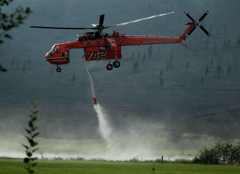 A helicopter descends in the Golden Eagle Subdivsion to refill with water from a pond while battling the Beaver Creek Fire on Saturday, Aug. 17, 2013 north of Hailey, Idaho.(AP Photo/Times-News, Ashley Smith) Mandatory Credit Photo: AP