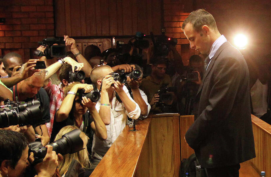 FILE- In this photo taken Friday, Feb. 22, 2013 photographers take photos of Olympic athlete Oscar Pistorius as he stands in the dock during his bail hearing at the magistrates court in Pretoria, South Africa.  According to reports Sunday Aug. 18, 2013, Pistorius is expected to be indicted on a main charge of premeditated murder of his girlfriend, Reeva Steenkamp. on upcoming Monday at Pretoria Magistrate's Court, prosecutors say, confirming they will maintain the charge they initially laid against Pistorius. Photo: AP