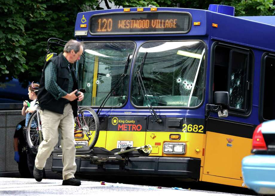 An official walks next to a King Co. Metro bus with multiple bullet holes in its windshield and side window, after a bus driver was shot Monday, Aug. 12, 2013, in downtown Seattle. A man who had shot the driver of another bus was shot by officers after he boarded the bus shown here. Photo: AP