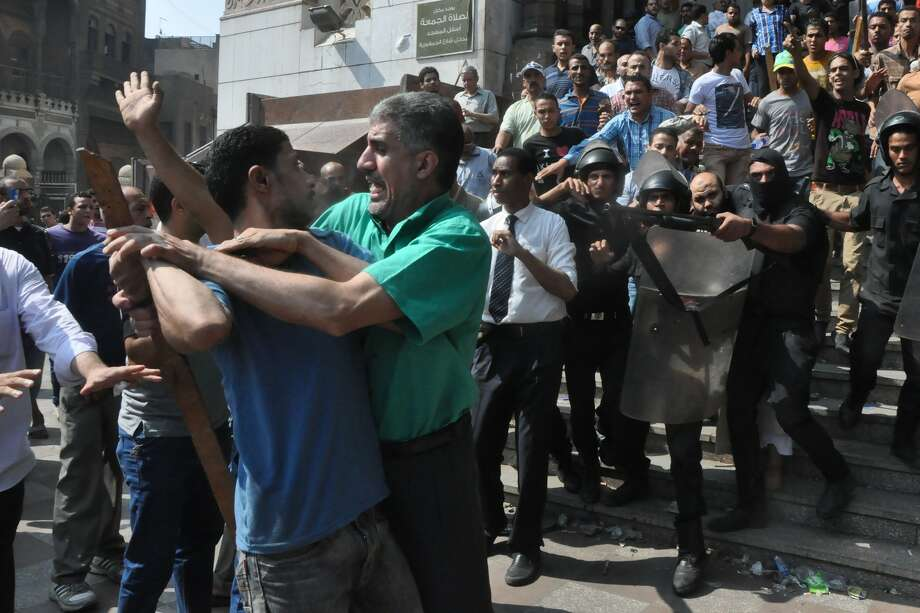 Egyptians security forces escort an Islamist supporter of the Muslim Brotherhood out of the al-Fatah mosque and through angry crowds, after hundreds of Islamist protesters barricaded themselves inside the mosque overnight, following a day of fierce street battles that left scores of people dead, near Ramses Square in downtown Cairo, Egypt, Saturday, Aug. 17, 2013. Authorities say police in Cairo are negotiating with people barricaded in a mosque and promising them safe passage if they leave. Muslim Brotherhood supporters of Egypt's ousted Islamist president are vowing to defy a state of emergency with new protests today, adding to the tension. Photo: AP