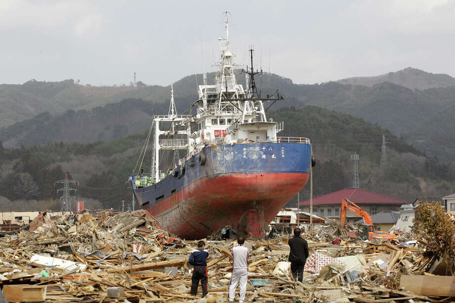 Survivors look at a ship among the rubble at a March 11 earthquake and tsunami-destroyed area in Kesennuma, Miyagi prefecture, Japan. The stranded fishing boat that became a symbol of the devastation of Japan's 2011 tsunami has long divided a northeastern coastal city - between those who wanted to keep it as a monument of survival and those who wanted a painful reminder gone. Last week, the city announced it will be torn down after a heated debate and citywide vote. Photo: AP