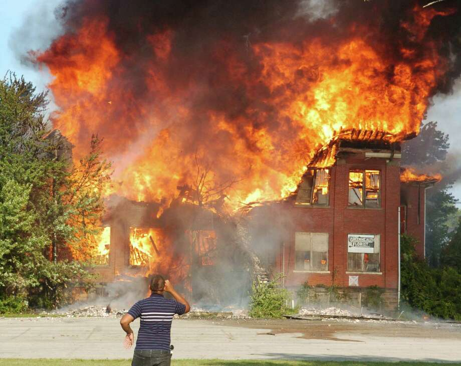 An Ashtabula, Ohio, man takes a picture of a massive fire at a former school building along West Avenue in Ashtabula late Saturday, Aug.17, 2013. Photo: AP