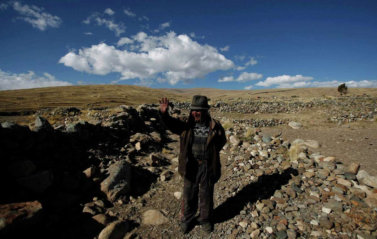 Carmelo Flores Laura, a native Aymara, waves to people near his home in the village of Frasquia, Bolivia, Tuesday, Aug. 13, 2013. If Bolivia's public records are correct, Flores is the oldest living person ever documented. They say he turned 123 a month ago. To what does the cattle and sheepherder owe his longevity?