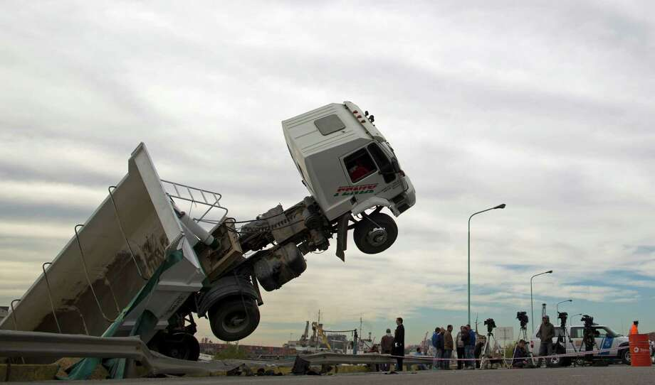 Reporters gather around a truck that was involved in a traffic accident in Buenos Aires, Argentina, Monday, Aug. 12, 2013. The truck driver lost control of his vehicle after crashing with a car ending up suspended above the Rio de la Plata river bank. No injuries where reported. Photo: AP
