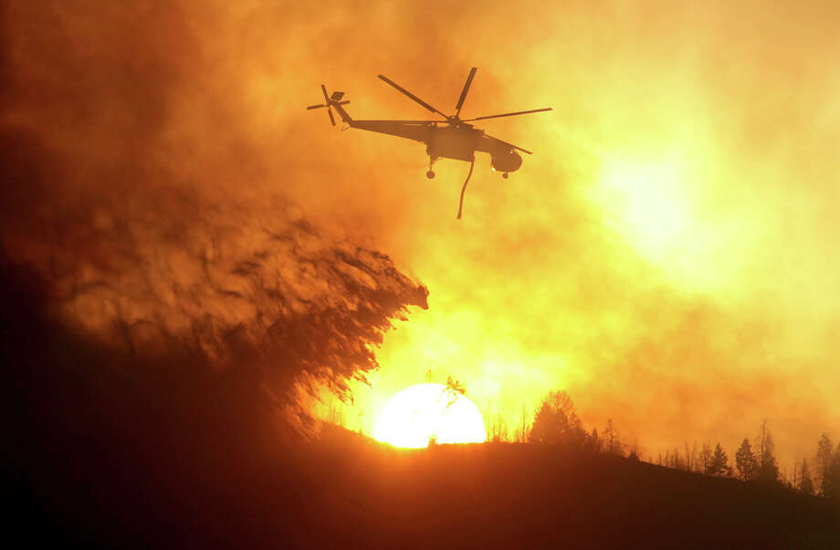 A helicopter makes a drop while battling the Beaver Creek Fire on Saturday, Aug. 17, 2013 north of Hailey, Idaho.(AP Photo/Times-News, Ashley Smith) Mandatory Credit Photo: AP