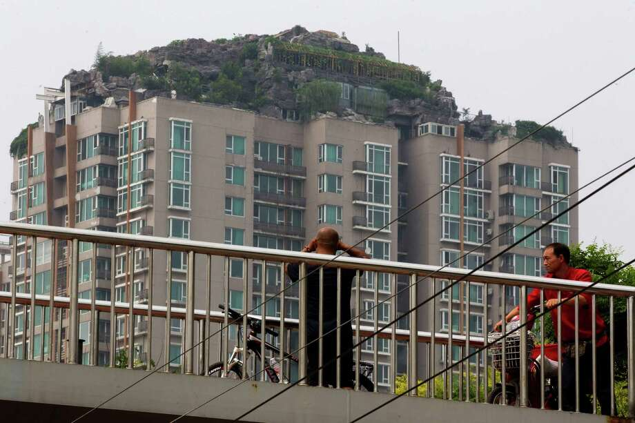 A man looks at a roof top villa with binoculars from an overhead bridge in Beijing, China, Tuesday, Aug. 13, 2013. Beijing authorities are planning to demolish the bizarre rooftop villa embedded in rocks, trees and bushes that allegedly was built illegally atop a 26-story apartment block in the capital. Photo: AP