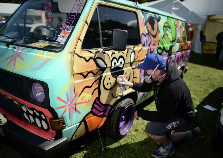 A man spray paints a VW campervan  during the In Praise Of All Things VW At The Annual Festiva at Harewood Housel on August 18, 2013 in Leeds, Yorkshire. The annual VW festival in its 9th year attracts around 15,000 people over the weekend, ending with the winners car parade on Sunday. Photo: Nigel Roddis, Getty Images / 2013 Getty Images