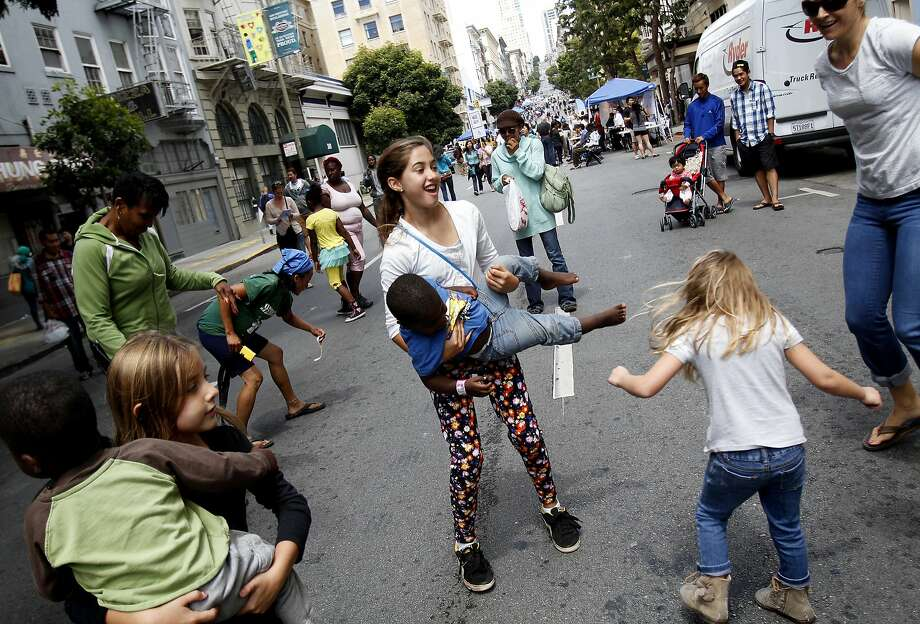 Grace Dealy (center), 10, dances with Zeke Ahlsten, 2, during Sunday Streets, a chance for people, not cars, to own the roadway. Photo: Sarah Rice, Special To The Chronicle