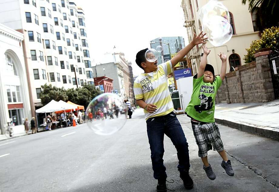 Nine-year-old Joshua Mendez (left) and Giovanni Escobar Ponce, 3, of San Francisco jump for bubbles in the Tenderloin. Photo: Sarah Rice, Special To The Chronicle