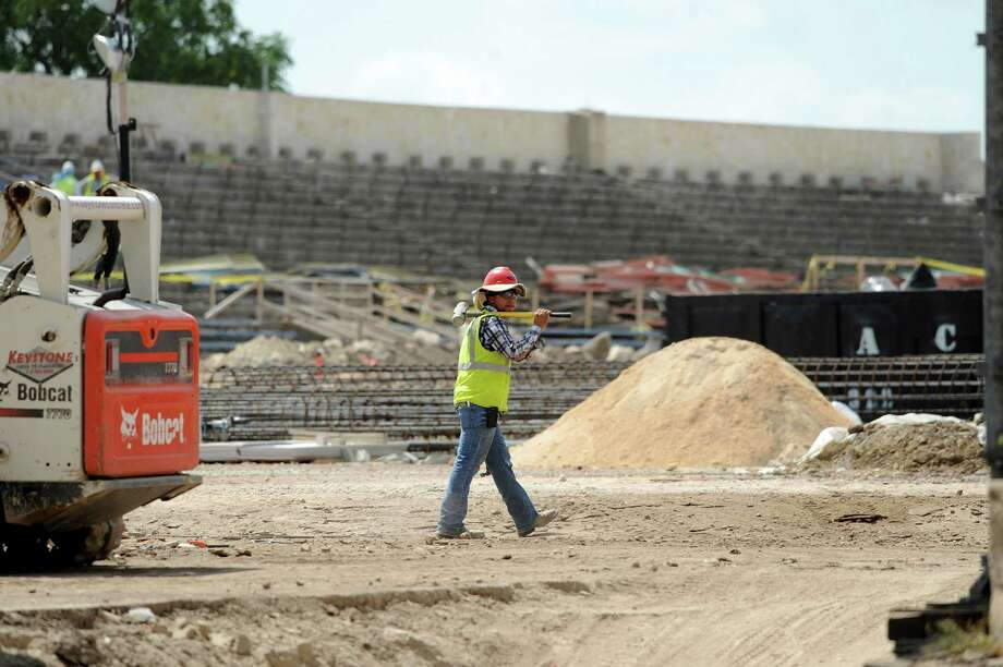 A construction worker makes his way through grounds of the San Antonio Independent School District's Alamo Stadium during renovations on Aug. 16, 2013. Photo: Billy Calzada, San Antonio Express-News / San Antonio Express-News