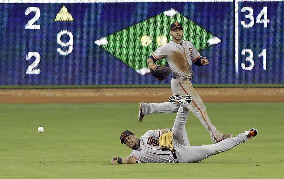"Bruce Bochy said there were ""balls bouncing everywhere,"" especially this one past the diving Andres Torres. Photo: Alan Diaz, Associated Press"