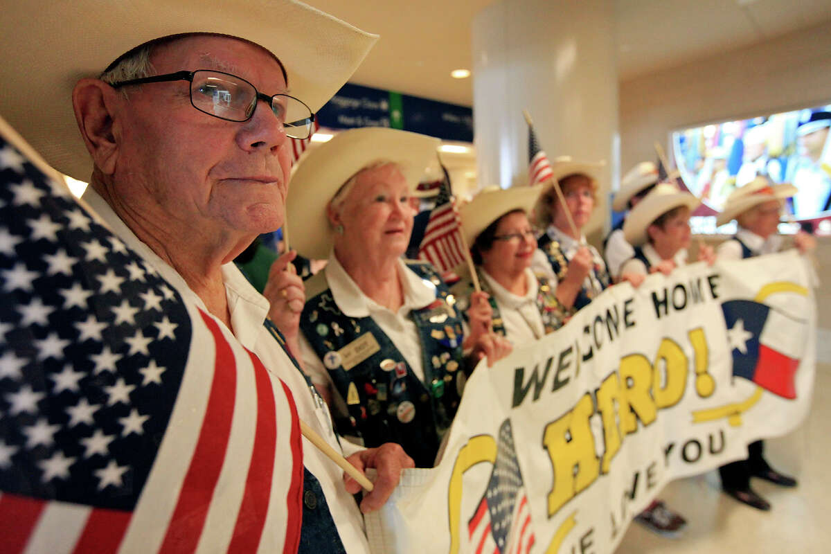 San Antonio International Airport Ambassador Volunteer John Heberling (left) and other ambassadors wait for the last Alamo Honor Fight to arrive at the airport Sunday Aug. 18, 2013. Forty-nine San Antonio area World War II veterans and 65 volunteers were part of the final flight. The Alamo Honor Flight is a nonprofit that gives World War II veterans an all expense paid trip to Washington D.C.