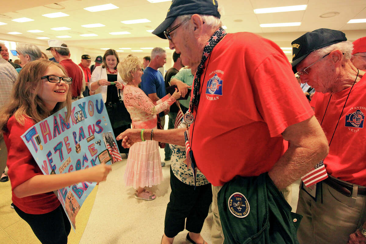 Halie Wilson, 11, (left) greets World War II Navy veteran William Towers, 87, (center) as he and other World War II veterans arrive at the San Antonio International Airport after taking part in the last Alamo Honor Flight Sunday Aug. 18, 2013. The Alamo Honor Flight is a nonprofit that gives World War II veterans an all expense paid trip to Washington D.C.