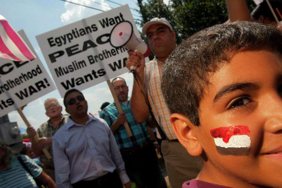 Raphael Hanna, 10, had an Egyptian flag painted on this cheek as more than 300 Coptic Christians from Saint Mary & Archangel Michael Coptic Orthodox Church and other Coptic parishes demonstrated at the corner of FM 529 and Highway 6 in support of the Egyptian Army and democracy in Egypt Sunday, Aug. 18, 2013, in Houston. 