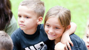Will Defeo, 6, of Trumbull, hugs Mackenzie Trafacante, 8, of Shelton, during the fourth annual Sunset Run for the Warriors at the Huntington Green in Shelton on Sunday, Aug. 18, 2013.