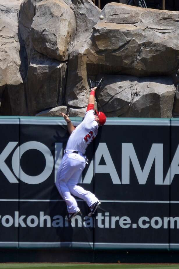 Angels outfielder Mike Trout is unable to grab a home run hit by L.J. Hoes of the Astros. Photo: Mark J. Terrill, Associated Press