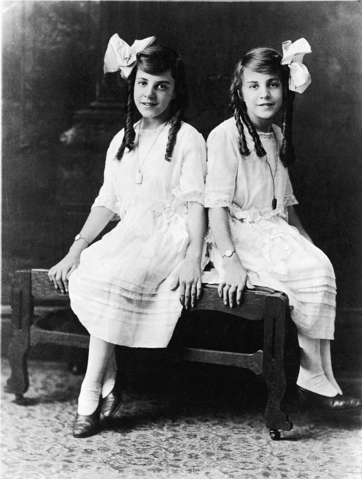 Portrait of British conjoined twins Violet Hilton (left) and Daisy Hilton dressed in matching dress with large bows in their hair, early 1920s.