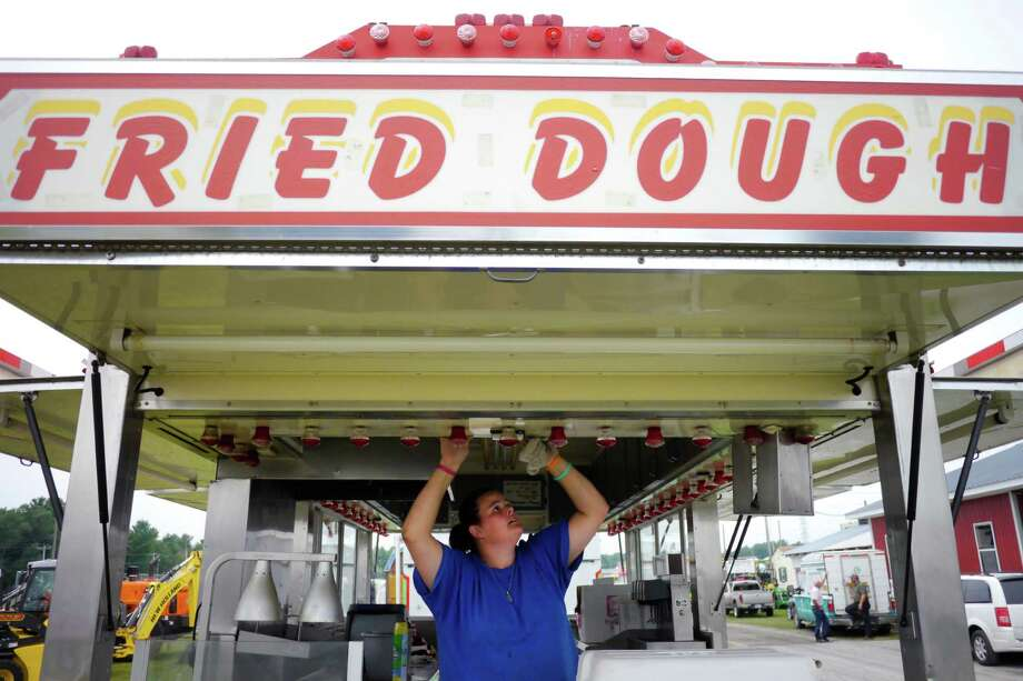 F&W Caterers employee Nicole Beaulieu from Portland, Conn.m cleans up the food stand she will work at the Washington County Fair grounds on set up day at the fair on Sunday, Aug. 18, 2013 in Greenwich, NY.  The fair opens for the week at 5pm on Monday.  (Paul Buckowski / Times Union) Photo: Paul Buckowski / 00023176A