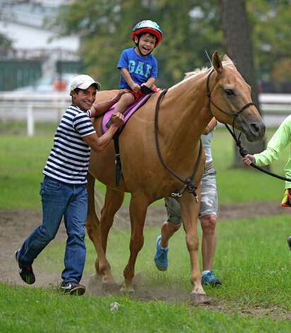 Jockey Alan Garcia, left gives his son Mathias a little instruction in riding Aug 18, 2013 at the Saratoga Race Course in Saratoga Springs, N.Y.    (Skip Dickstein/Times Union) Photo: SKIP DICKSTEIN