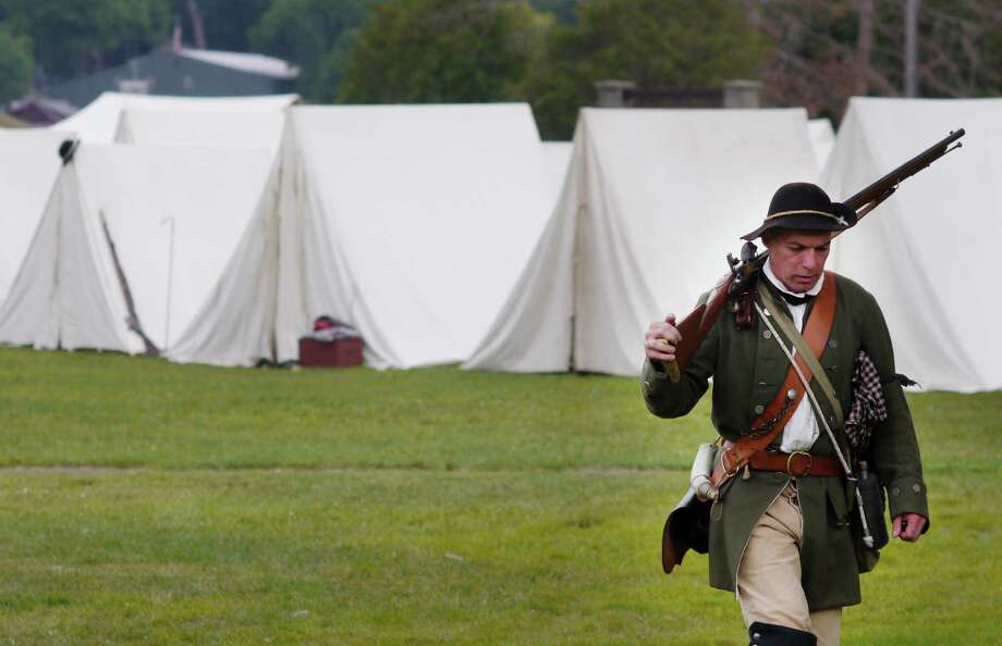 Dave Corliss from Clifton Park, portraying a member of the New York Provincial army makes his way across the grounds during a French and Indian War encampment put on by re-enactors on Sunday, Aug. 18, 2013 in Lake George, NY.  Members of the New York Provincial army were colonists from New York who fought on the side of the British.   Re-enactors representing British, French and their Native American allies camped at the Lake George Battlefield Park to demonstrate what it was like to live and battle in the wilderness of 1757.  Fort William Henry, located in Lake George, was the scene in 1757, where the British surrendered to the French after the French attacked the fort.  (Paul Buckowski / Times Union) Photo: Paul Buckowski / 00023535A