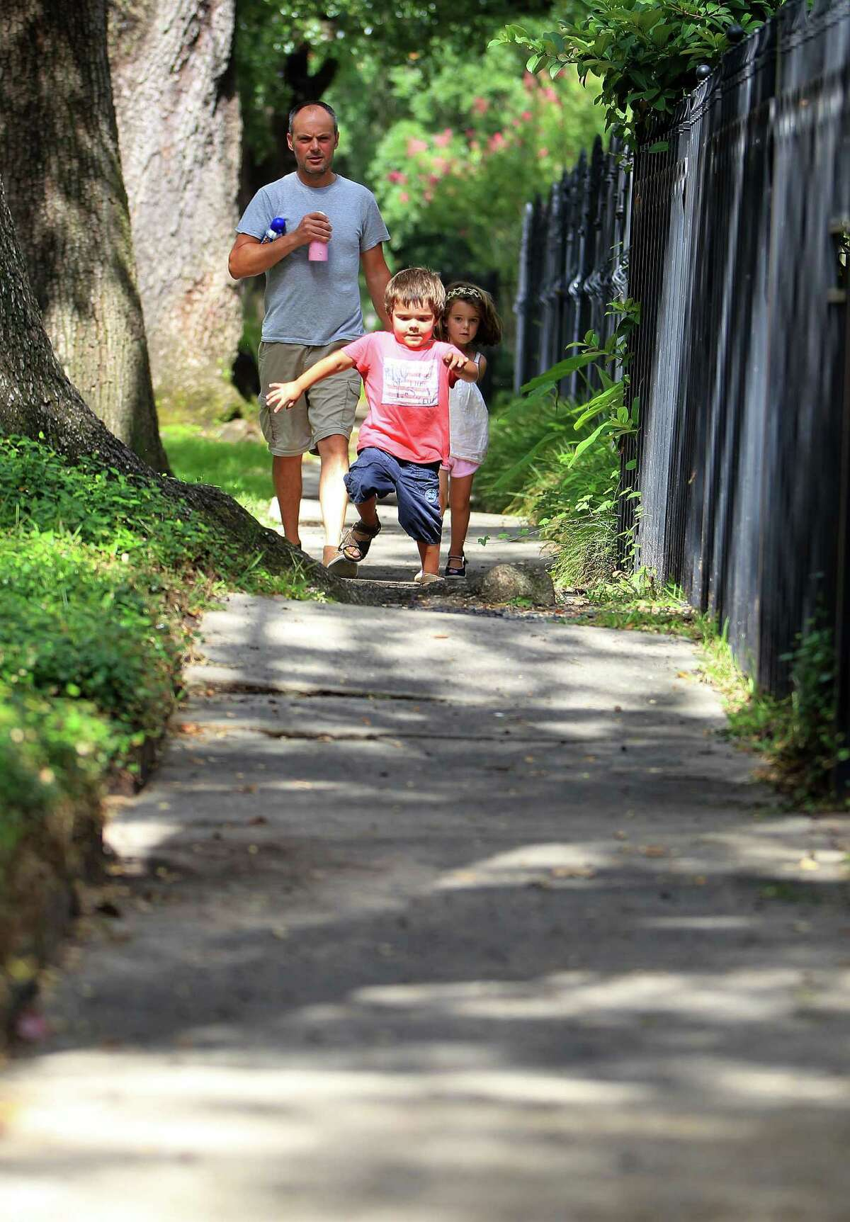 Daniel Spibey walks with his children Hatty, 5, and Ned, 3, along Bayland in Woodland Heights. Sidewalks in such disrepair can present real dangers for disabled or elderly residents.