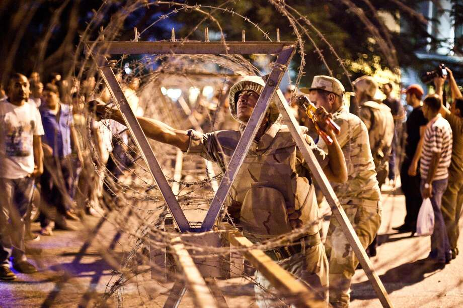Egyptian army soldiers remove barbed wire that had been surrounding the Supreme Constitutional Court in Cairo ahead of planned demonstrations on Sunday that were canceled by Islamist demonstrators. Photo: VIRGINIE NGUYEN HOANG, Stringer / VIRGINIE NGUYEN HOANG/AFP