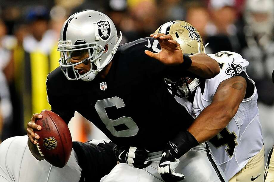 Terrelle Pryor, who completed only one pass against the Saints, is sacked by New Orleans' Glenn Foster on Friday. Photo: Stacy Revere, Getty Images