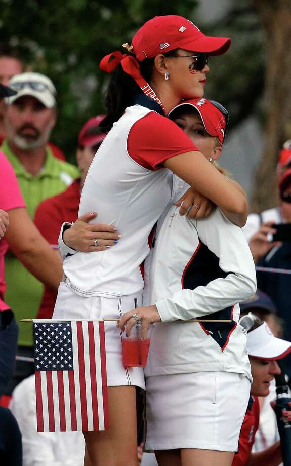 United States' Michelle Wie, left, hugs teammate Morgan Pressel on the 18th green after Wie lost her singles match against Europe's Caroline Hedwall, from Sweden, to allow Europe to retain the Solheim Cup during the golf tournament ,Sunday, Aug. 18, 2013, in Parker, Colo. (AP Photo/Chris Carlson)  ORG XMIT: COEA141 Photo: Chris Carlson / AP