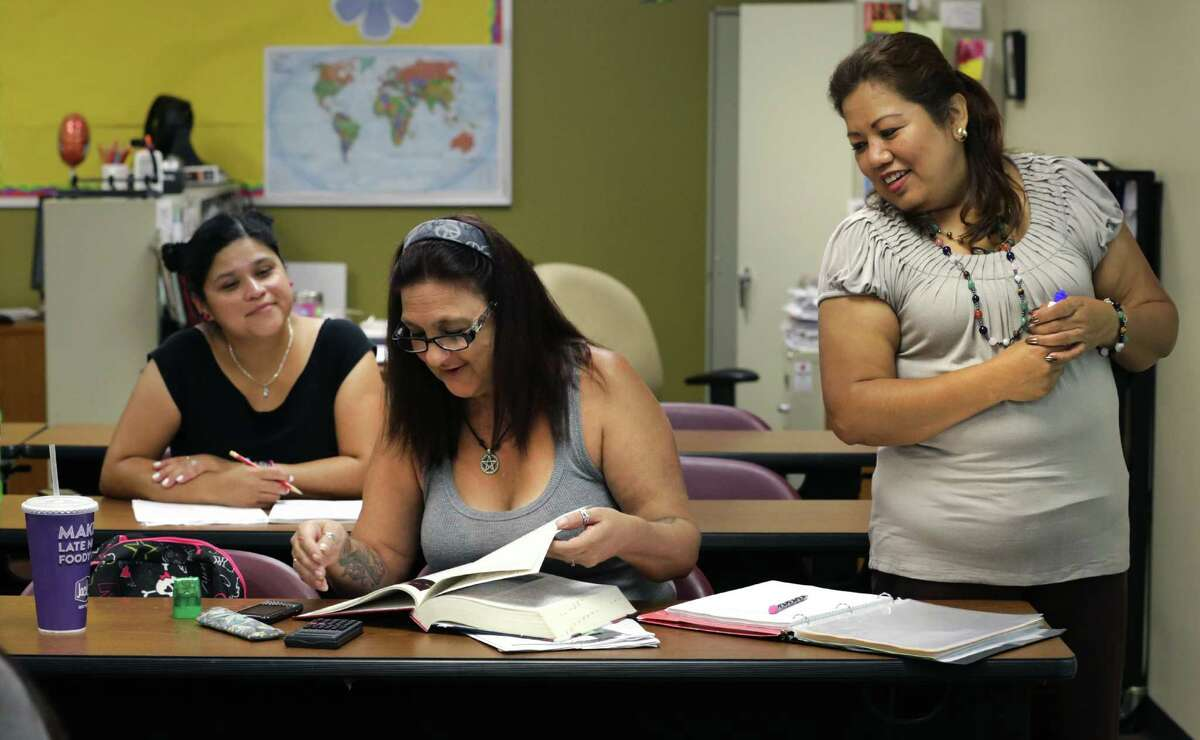 GED students Linda Mackintosh, center, and Priscilla Dominguez, left, attend a class at WorkForce Solutions Alamo taught by Maria Carmen Sanchez, right, on Wednesday, August 14, 2013. The GED program will be changing to a more computerized system for the students.