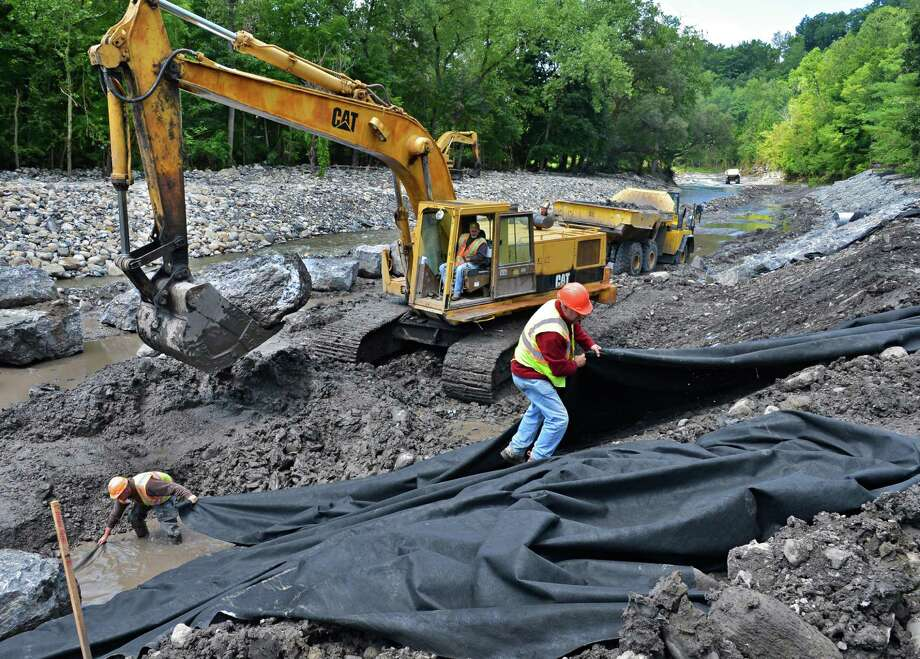 Crews lay down a geo fabric and stack extra heavy stones to restore the stream bed and road slope along the Otsquago Creek Wednesday Aug. 14, 2013, in Fort Plain, NY.  (John Carl D'Annibale / Times Union) Photo: John Carl D'Annibale / 00023506A